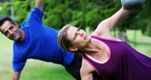 Mature couple exercising with kettlebell in the park