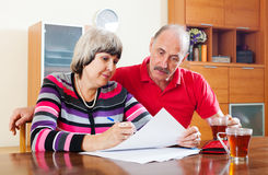 Mature couple fills in questionnaire together Royalty Free Stock Photo