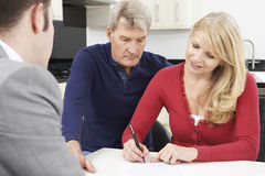 Mature Couple With Financial Advisor Signing Document At Home Stock Image
