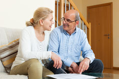 Mature couple with financial documents. Happy elderly couple with financial documents on sofa in home interior royalty free stock photography
