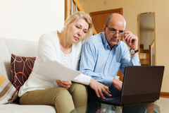 Mature couple with financial documents and laptop Royalty Free Stock Image