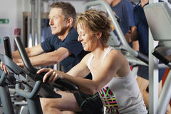 Mature couple at fitness centre. Mature couple working out at fitness centre on excercise bikes Stock Image