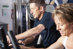 Mature couple at fitness centre. Mature couple working out at fitness centre Stock Photo