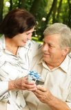 Mature couple with gift stock image