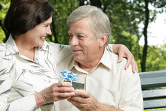 Mature couple with gift Stock Images