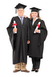 Mature couple in graduation gowns with diplomas Stock Image