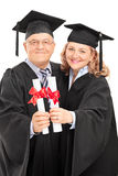 Mature couple in graduation gowns holding diplomas Royalty Free Stock Photography