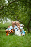 Mature couple with guitar   in park Stock Images