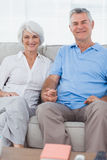 Mature couple hand in hand sitting on a couch Royalty Free Stock Images