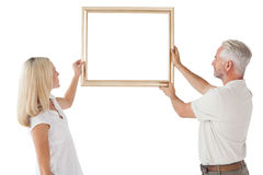 Mature couple hanging up picture frame Stock Image