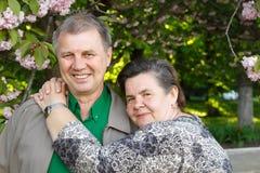 Mature couple happy hug in spring garden. Mature couple cheerful hug in spring garden Stock Photo