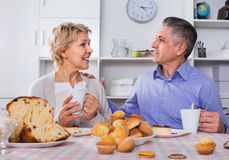 Mature couple have an afternoon snack with fresh muffins and cake. Glad cheerful mature couple have an afternoon snack with fresh muffins and cake in their home stock photos