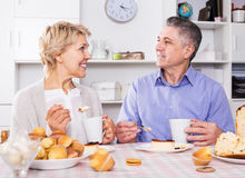 Mature couple have breakfast. Mature married couple have breakfast and have coffee with cakes at table in kitchen Stock Image