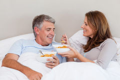 Mature couple having breakfast in bed Stock Images