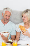 Mature couple having breakfast in bed Royalty Free Stock Photo