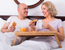Mature couple having breakfast in bed. Joyful smiling senior couple having healthy breakfast in bed in the morning Royalty Free Stock Images