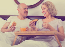 Mature couple having breakfast in bed Royalty Free Stock Photography