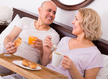 Mature couple having breakfast in bed Stock Photos