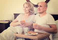 Mature couple having breakfast in bed Royalty Free Stock Images