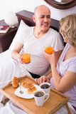 Mature couple having breakfast in bed Royalty Free Stock Photos