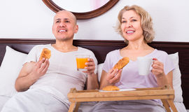 Mature couple having breakfast in bed Stock Photo