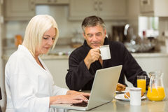 Mature couple having breakfast together woman using laptop Royalty Free Stock Images