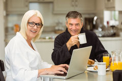 Mature couple having breakfast together woman using laptop Royalty Free Stock Image