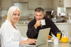 Mature couple having breakfast together woman using laptop Royalty Free Stock Photography