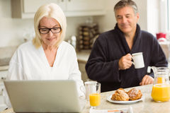 Mature couple having breakfast together woman using laptop Stock Photos