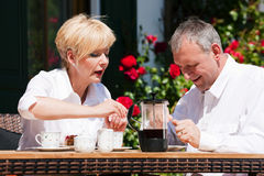 Mature couple having coffee on porch stock photography