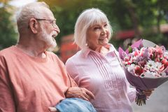 Mature couple having date outdoors. Side view of smiling man walking with his wife on street. Old lady is carrying bouquet of flowers with delight Stock Photo