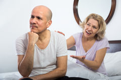 Mature couple having quarrel in bedroom Stock Images