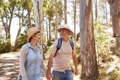 Mature Couple Hiking Along Forest Path Together Stock Image