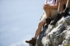 Mature couple, in hiking boots and shorts, sitting at edge of rock, looking at scenery, low-section stock images