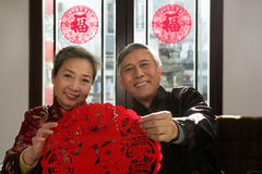 Mature couple holding chinese cut paper on New year Royalty Free Stock Images