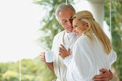 Mature couple holding coffee cups by copy space Stock Photo