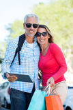 Mature couple holding digital tablet and shopping bags Stock Image