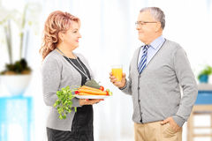 Mature couple holding a dish full of vegetables looking at each Royalty Free Stock Photo