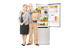 Mature couple holding groceries in front of a fridge Stock Image