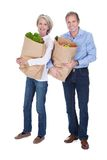 Mature Couple Holding Grocery Stock Images