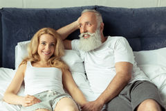 Mature couple holding hands and relaxing on bed at home Stock Photos