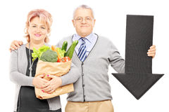 Mature couple holding a paper bag full of groceries and big blac. K arrow pointing down isolated on white background Stock Image