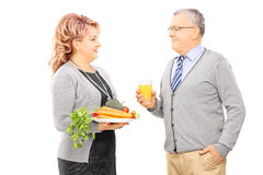 Mature couple holding plate full of vegetables looking at each o Stock Photos