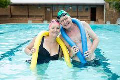 Mature couple holding pool noodles Royalty Free Stock Images