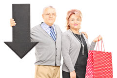 Mature couple holding shopping bags and big black arrow pointing Royalty Free Stock Images