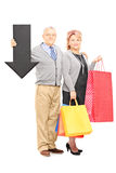 Mature couple holding shopping bags and big black arrow pointing Stock Photography
