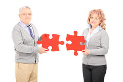 Mature couple holding two pieces of puzzle Royalty Free Stock Images