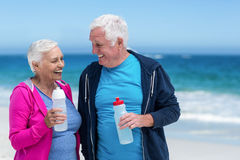 Mature couple holding water bottles together Stock Photos