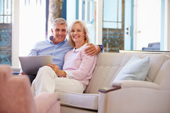 Mature Couple At Home In Lounge Using Laptop Computer Stock Photos