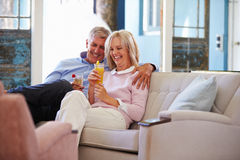 Mature Couple At Home Relaxing In Lounge With Cold Drinks Stock Image